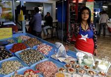 Una vendedora se para junto a su puesto de diversos alimentos marinos en el mercado de Coquimbo, Chile. 14 de junio 2015. El Índice de Precios al Consumidor (IPC) en Chile habría subido un 0,3 por ciento en febrero, debido a alzas puntuales en alimentos y ajustes de tipo estacional, mostró el martes un sondeo de Reuters. REUTERS/David Mercado - RTX1GHBQ