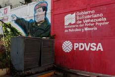 El logo de la petrolera estatal venezolana PDVSA se ve junto a un mural que representa al fallecido presidente venezolano, Hugo Chávez, en una gasolinera en Caracas, Venezuela. 2 de marzo de 2017. La estatal venezolana Petróleos de Venezuela (PDVSA) pasó al menos una década intentando mejorar relaciones comerciales e impulsar sus ventas a las refinerías de India, un país que una vez recibió con vítores al fallecido líder socialista Hugo Chávez. REUTERS/Carlos Garcia Rawlins