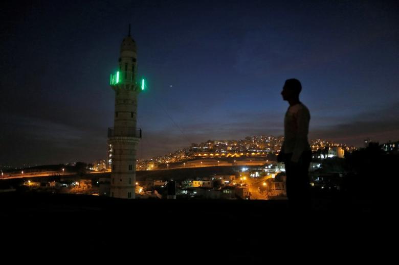 A man stands near a mosque opposite to a neighborhood in east Jerusalem November 13, 2016. REUTERS/Ammar Awad