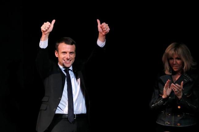 3月9日、調査会社ハリス・インタラクティブが公表したフランス大統領選に関する世論調査によると、第1回投票で中道系独立候補のマクロン前経済相が、極右政党・国民戦線(FN)のルペン党首を上回る票を獲得し、決選投票でルペン氏に勝利することが見込まれている。写真は8日パリの国際女性デーのイベントに妻(右)と参加したマクロン氏(左)(2017年 ロイター/Gonzalo Fuentes)