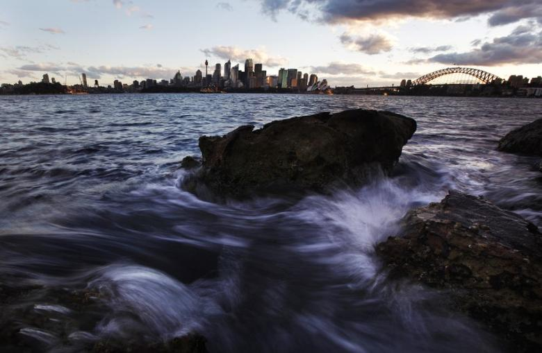 Small waves crash over rocks across the harbour from the Sydney city skyline May 23, 2011. REUTERS/Tim Wimborne/Files