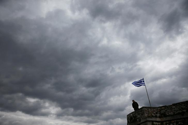 A man looks down as a Greek national flag flutters atop one of the bastions of the 17th century fortress of Palamidi under an overcast sky at the southern port city of Nafplio, Greece, February 19. 2017. REUTERS/Alkis Konstantinidis
