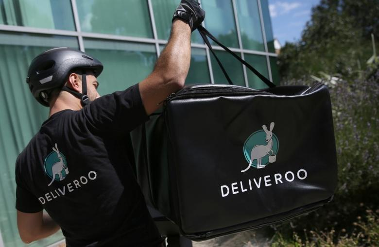 A Deliveroo worker loads his bicycle after making a delivery in London, Britain August 15, 2016. REUTERS/Neil Hall