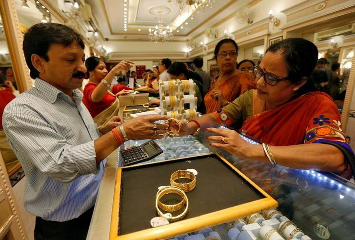 A salesman shows gold bangles to a customer at a jewellery showroom during Dhanteras, a Hindu festival associated with Lakshmi, the goddess of wealth, in Kolkata, India October 28, 2016. REUTERS/Rupak De Chowdhuri/File photo