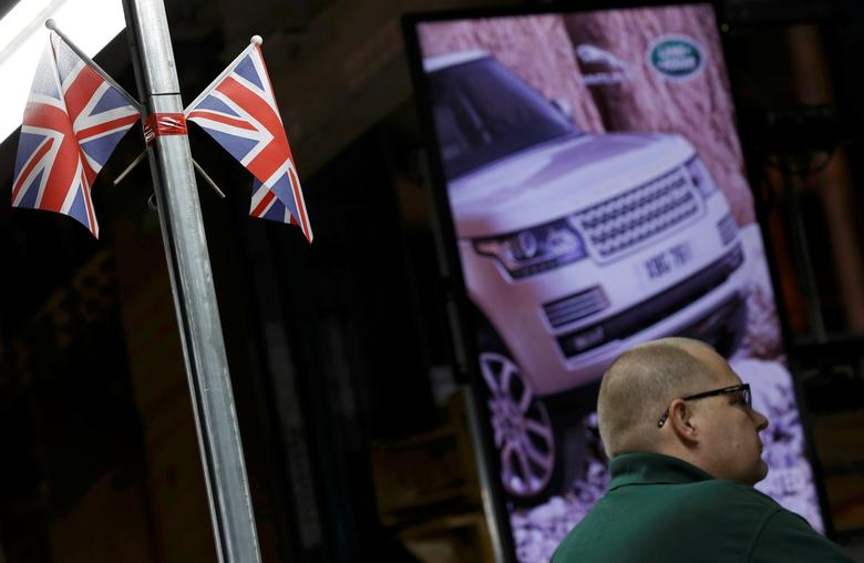 FILE PHOTO: A worker stands under Union Flags at the Jaguar Land Rover facility in Solihull, Britain, January 30, 2017. REUTERS/Darren Staples/File Photo