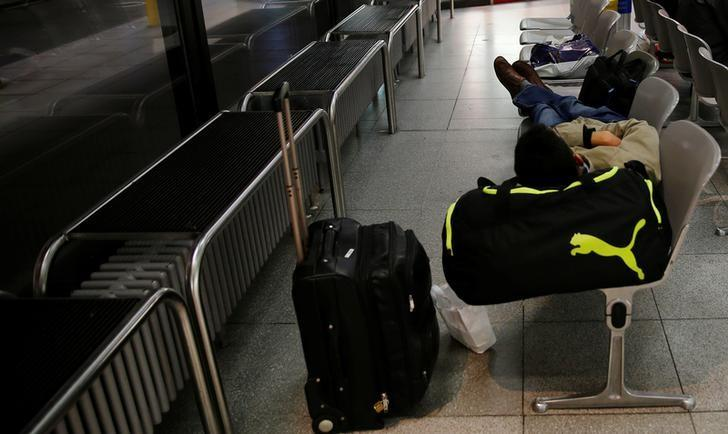 A man lies on chairs during a warning strike by ground services, security inspection and check-in staff at Tegel airport in Berlin, Germany, March 10, 2017. REUTERS/Hannibal Hanschke