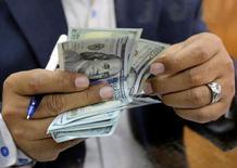 Una persona contando dólares en una casa de cambios en El Cairo, mar 7, 2017. El euro escaló el viernes a un máximo de tres semanas contra el dólar, debido a un reporte que asegura que el Banco Central Europeo discutió la posibilidad de subir las tasas de interés antes de finalizar su programa de alivio cuantitativo.  REUTERS/Mohamed Abd El Ghany