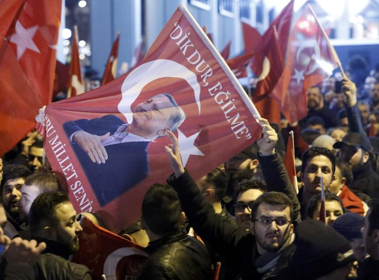 Demonstrators with banners of Turkish President Recep Tayyip Erdogan gather outsidethe Turkish consulate to welcome the Turkish Family Minister Fatma Betul Sayan Kaya, who decided to travel to Rotterdam by land after Turkish Foreign Minister Mevlut Cavusoglu's flight was barred from landing by the Dutch government, in Rotterdam, Netherlands March 11, 2017.     REUTERS/Yves Herman