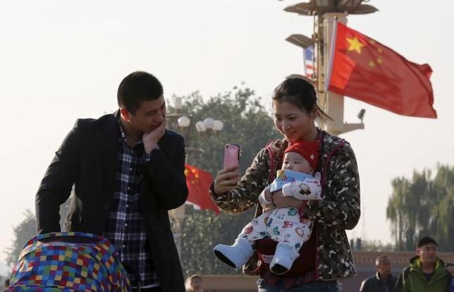 3月11日、中国の国家衛生計画出産委員会は、同国の出生率が2020年にかけて上昇するとの見通しを明らかにした。すべての夫婦に2人目の子供を認める「二人っ子政策」が昨年、「著しい成果」を挙げたという。写真は北京天安門で写真を撮る親子。2015年11年撮影(2017年 ロイター/Kim Kyung-Hoon)