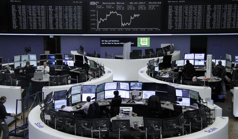 Traders work at their desks in front of the German share price index, DAX board, at the stock exchange in Frankfurt, Germany, March 8, 2017. REUTERS/Staff/Remote