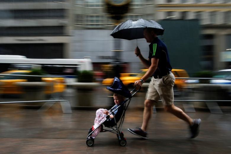 A man runs with his son in a stroller, during a pouring rain in Manhattan, New York, U.S., August 20, 2016. REUTERS/Eduardo Munoz