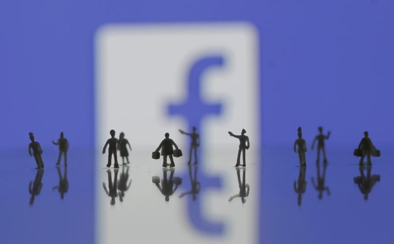3D-printed models of people are seen in front of a Facebook logo in this photo illustration taken June 9, 2016. REUTERS/Dado Ruvic/Illustration - RTSGTLZ