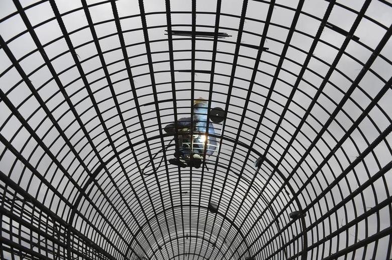 2013年7月,安徽合肥一处住宅建设工地的工人在焊接钢筋网。REUTERS/Stringer