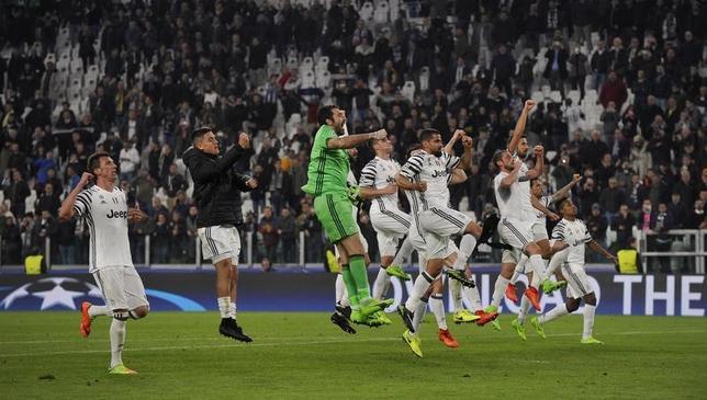 3月14日、サッカーの欧州チャンピオンズリーグ(CL)でユベントス(イタリア)はポルト(ポルトガル)に1─0で勝利。2戦合計3─0で8強進出を果たした。写真は勝利を喜ぶユベントスの選手たち(2017年 ロイター)