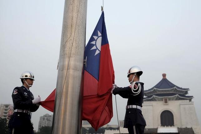 3月15日、ロイターが入手した台湾の「4年ごとの国防計画見直し2017年版」によると、台湾は、中国による軍事的脅威が高まっているとの認識を示している。写真は昨年4月、台北の自由広場で台湾国旗を下げる台湾軍儀仗兵(2017年 ロイター/Tyrone Siu)
