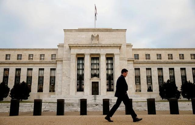 FILE PHOTO: A man walks past the Federal Reserve Bank in Washington, D.C., U.S. December 16, 2015.   REUTERS/Kevin Lamarque