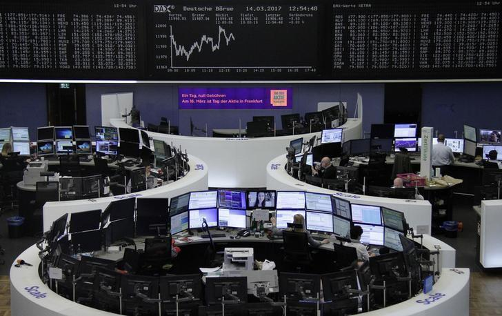 Traders work at their desks in front of the German share price index, DAX board, at the stock exchange in Frankfurt, Germany, March 14, 2017. REUTERS/Staff/Remote