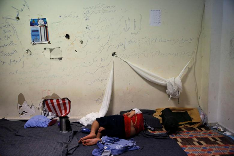 FILE PHOTO: A boy sleeps inside the disused Hellenikon airport where refugees and migrants are temporarily housed in Athens, Greece July 13, 2016. REUTERS/Alkis Konstantinidis/File Photo