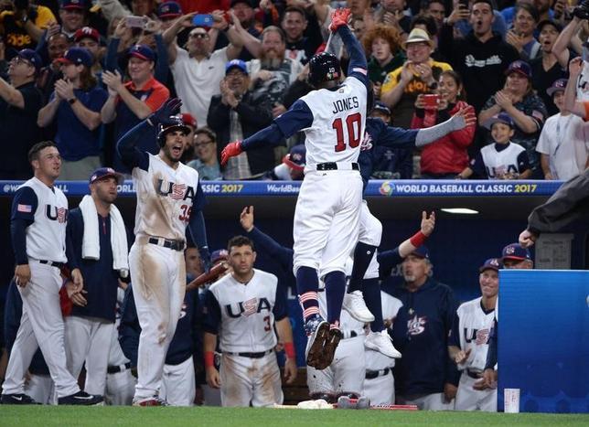 3月15日、野球の国・地域別対抗戦、第4回WBC2次リーグF組、米国はベネズエラに4─2で勝利を収めた。アダム・ジョーンズ外野手(中央)が8回にソロホームラン(2017年 ロイター/Orlando Ramirez-USA TODAY Sports)