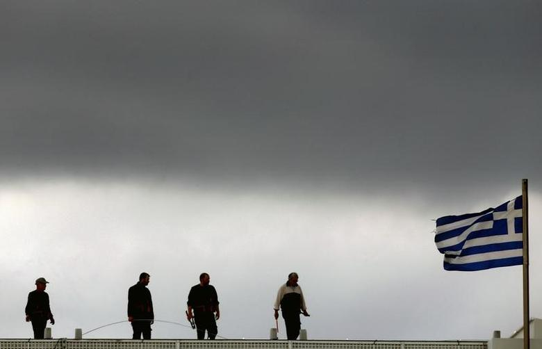 Workers are seen atop a building next to a Greece flag in Syntagma square in Athens March 10, 2015.   REUTERS/Yannis Behrakis