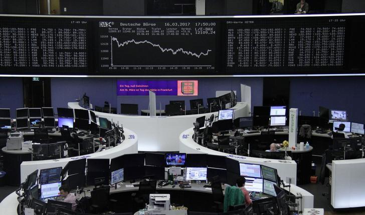 Traders work at their desks in front of the German share price index, DAX board, at the stock exchange in Frankfurt, Germany, March 16, 2017. REUTERS/Staff/Remote/Files