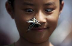 Foto de archivo de un niño chino reaccionando luego de que una mariposa se posara en su nariz. Sep 26, 2015.  Investigadores dijeron el jueves que un estudio que usó imágenes tridimensionales de cientos de personas de ascendencia del este y sur de Asia, de África Occidental y del norte de Europa indicó que el clima local, en especial la temperatura y la humedad, tuvo un papel clave en determinar la forma de la nariz. REUTERS/Stringer