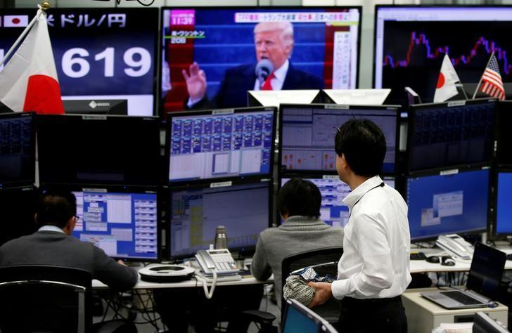 资料图片:1月23日,东京一家外汇交易公司,雇员身边的屏幕显示的是美国总统特朗普和日元兑美元汇率。REUTERS/Toru Hanai