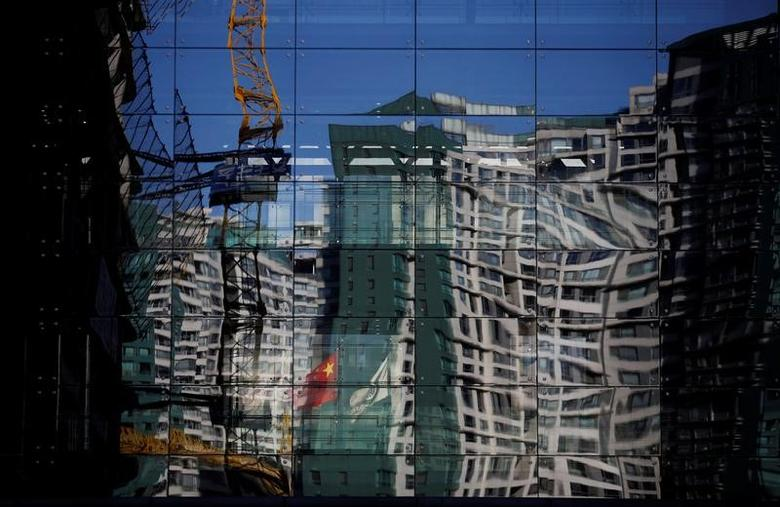 A construction site and a residential building are reflected on the glass wall of a building in Beijing, December 15, 2014. REUTERS/Kim Kyung-Hoon/File Photo