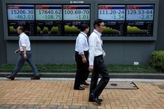 Peatones caminan frente a unas pantallas que muestra el índice Nikkei y otras divisas afuera de una correduría en Tokio, Japón. 6 de julio de 2016. El índice Nikkei de la bolsa de Tokio cayó el viernes en una sesión en la que el yen se mantuvo estable frente al dólar después de que la Reserva Federal de Estados Unidos señaló una menor cantidad de alzas de las tasas de interés este año que la previsto por algunos inversores.REUTERS/Issei Kato