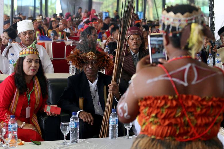 Participants take photos on the sidelines of an indigenous people's gathering, near Medan, Sumatra Island, Indonesia March 17, 2017. Antara Foto/Irsan Mulyadi/via REUTERS