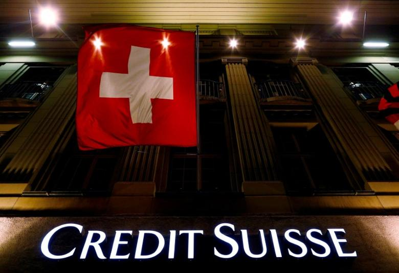 FILE PHOTO -  The logo of Swiss bank Credit Suisse is seen below the Swiss national flag at a building in the Federal Square in Bern, Switzerland May 15, 2014.   REUTERS/Ruben Sprich/File Photo