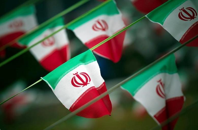 FILE PHOTO: Iran's national flags are seen on a square in Tehran February 10, 2012. REUTERS/Morteza Nikoubazl/File Photo