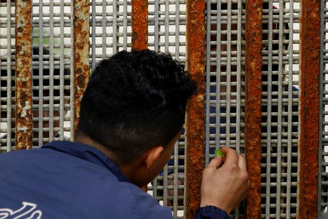 A man, who was deported from the U.S. seven months ago, receives candy from his nephew across a fence separating Mexico and the United States as photographed from Tijuana, Mexico, March 4, 2017. Picture taken from the Mexican side of the border.  REUTERS/Jorge Duenes/Files