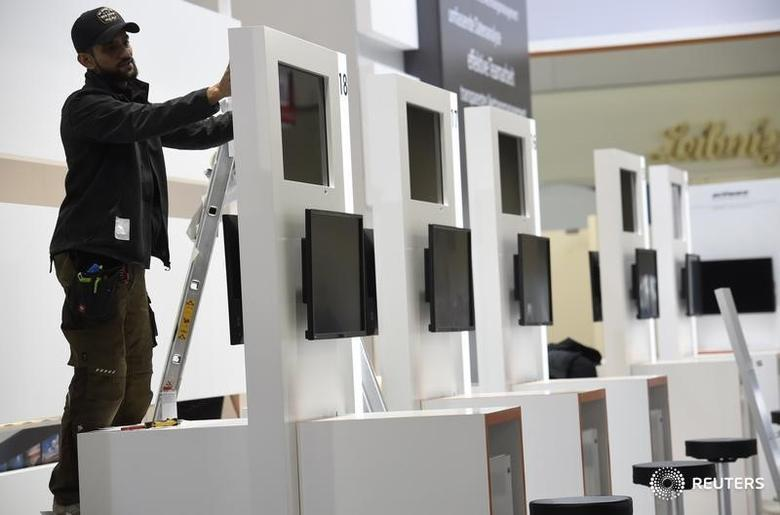 A worker installs touchscreens at the booth of Elo during preparations at the CeBit computer fair, which will open its doors to the public on March 20, at the fairground in Hanover, Germany, March 18, 2017.  REUTERS/Fabian Bimmer - RTX31MU6