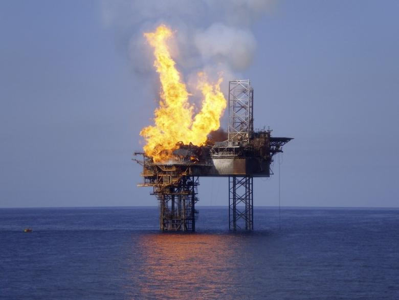 Fire burns on the partially collapsed Montara well head platform and the West Atlas mobile offshore drilling unit in the Timor Sea, about 250 km (155 miles) off the far north Kimberley coast of Western Australia state, in this November 3, 2009 handout picture.  REUTERS/PTTEP/Handout