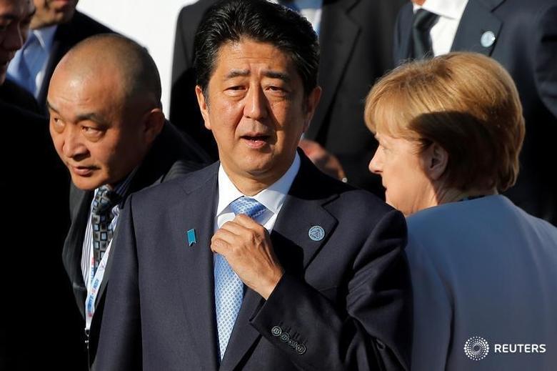 German Chancellor Angela Merkel walks behind Japan's Prime Minister Shinzo Abe as leaders arrive for a family photo during the Asia-Europe Meeting (ASEM) summit just outside Ulaanbaatar, Mongolia, July 16, 2016.   REUTERS/Damir Sagolj - RTSI80A
