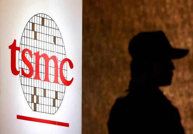 FILE PHOTO -  A security personnel stands near the logo of Taiwan Semiconductor Manufacturing Co. Ltd (TSMC) during an investor conference in Taipei, July 16, 2014.  REUTERS/Pichi Chuang/File Photo
