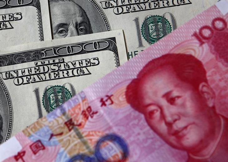 资料图片:2010年11月,美元和人民币。REUTERS/Petar Kujundzic