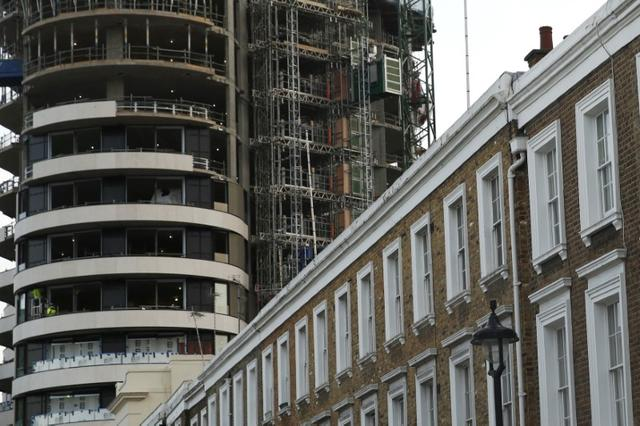 An apartment block is constructed behind a row of traditional properties in central London December 11, 2014. REUTERS/Luke MacGregor