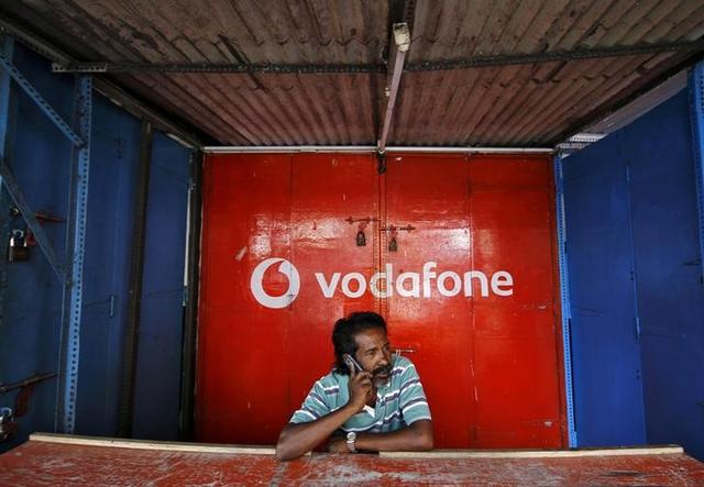FILE PHOTO: A retail shop owner speaks on his mobile phone outside his closed shop shutters painted with an advertisement for Vodafone at a market in Chennai, India, December 30, 2013.  REUTERS/Babu