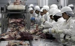 Trabajadores cortan la carne en una de las plantas de JBS, en Sao Paulo, Brasil. 9 de septiembre 2005.China suspendió de forma temporal las importaciones de carne brasileña a partir del 19 de marzo, tras el escándalo por el supuesto soborno de funcionarios sanitarios para permitir la venta del producto en mal estado, dijo el lunes una fuente. REUTERS/Paulo Whitaker/Files  (BRAZIL) - RTXBZX4