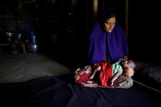 Rajuma Begum, 28, poses for a photograph with her one-month-old son Raihan inside their shelter in Kutupalang unregistered refugee camp in Cox's Bazar, Bangladesh, February 12, 2017.  REUTERS/Mohammad Ponir Hossain