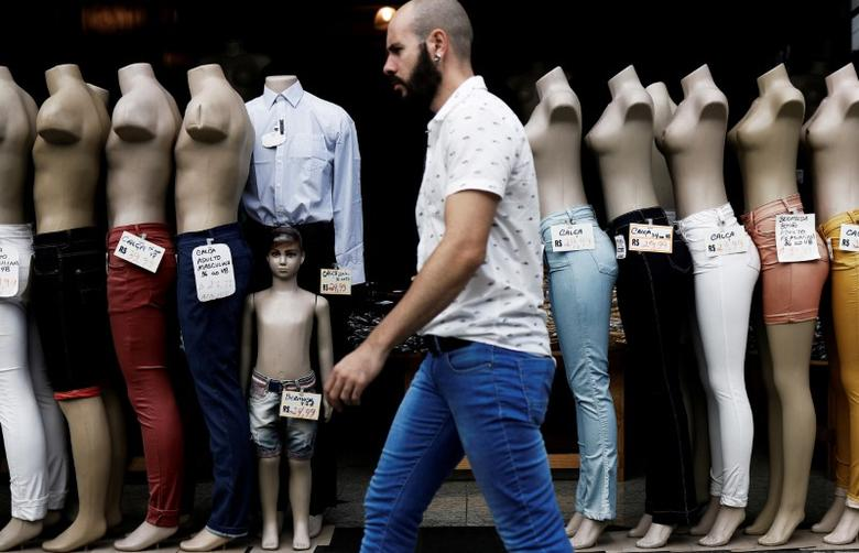 FILE PHOTO: A man walks past mannequins lined up at the entrance of a shop, in downtown Sao Paulo, Brazil March 15, 2017.  REUTERS/Nacho Doce/File Photo