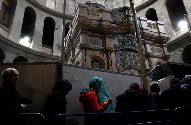 Visitors stand near the newly restored Edicule, the ancient structure housing the tomb, which according to Christian belief is where Jesus's body was anointed and buried, at the Church of the Holy Sepulchre in Jerusalem's Old City March 20, 2017. REUTERS/Ronen Zvulun