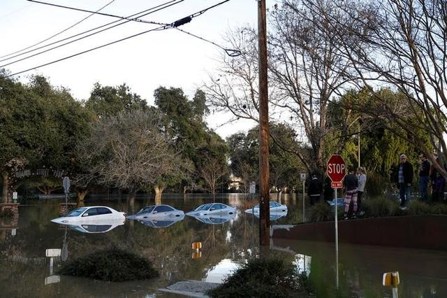 Vehicles are seen partially submerged in flood water at William Street Park after heavy rains overflowed nearby Coyote Creek in San Jose, California, U.S., February 21, 2017. REUTERS/Stephen Lam