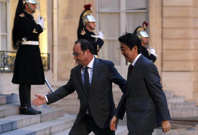 French President Francois Hollande (L) welcomes Japan's Prime Minister Shinzo Abe as he arrives at the Elysee Palace in Paris, France, March 20, 2017.  REUTERS/Philippe Wojazer