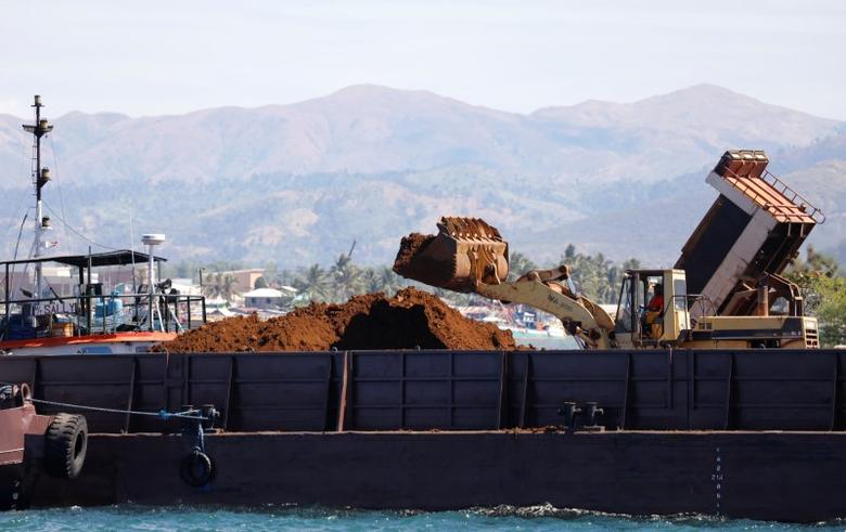 A back hoe loads soil containing nickel-ore minerals into a barge in the mining town of Sta Cruz Zambales in northern Philippines February 8, 2017. Picture taken February 8, 2017.   REUTERS/Erik De Castro