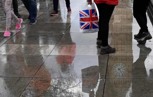 The Elizabeth Tower, commonly known as Big Ben, together with walkers are seen reflected in a puddle in London, Britain, March 20, 2017.  REUTERS/Toby Melville