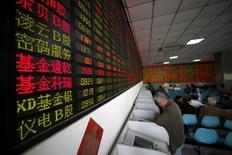 En la foto de archivo, inversores miran pantallas de computadora que muestran información de mercados en un operador bursátil en ShangháiLas acciones chinas cerraron con un leve avance el martes, pero el apetito por el riesgo de los inversores fue restringido en medio de las señales de menor liquidez en el sistema bancario.REUTERS/Aly Song/File Photo