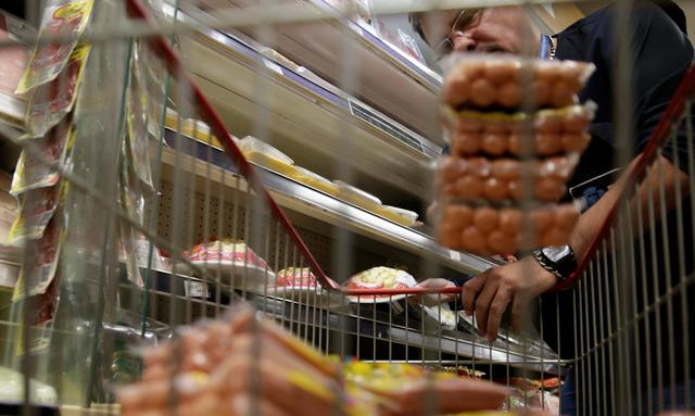 A member of the Public Health Surveillance Agency collects sausages to analyse in the laboratory, at a supermarket in Rio de Janeiro, Brazil, March 20, 2017. REUTERS/Ricardo Moraes